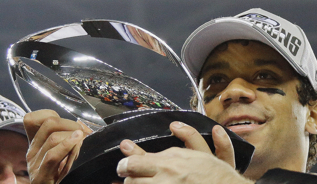 . Seattle Seahawks\' Russell Wilson holds up the George Halas Trophy after the NFL football NFC Championship game against the San Francisco 49ers, Sunday, Jan. 19, 2014, in Seattle. The Seahawks won 23-17 to advance to Super Bowl XLVIII. (AP Photo/Matt Slocum)