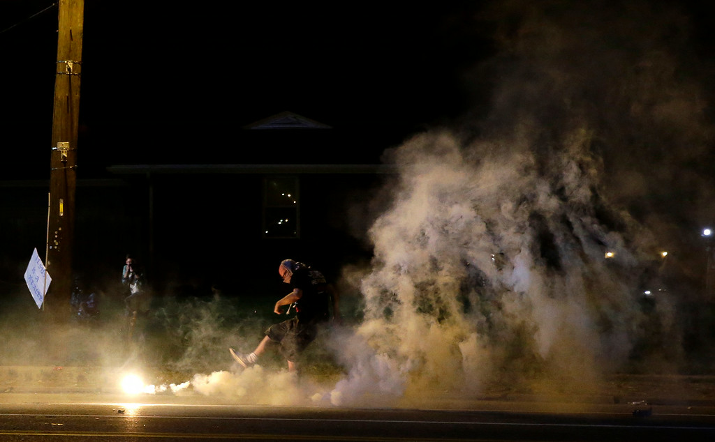 Description of . A protester kicks a smoke grenade deployed by police back in the direction of police, Wednesday, Aug. 13, 2014, in Ferguson, Mo. Protests in the St. Louis suburb rocked by racial unrest since a white police officer shot an unarmed black teenager to death turned violent Wednesday night, with people lobbing Molotov cocktails at police who responded with smoke bombs and tear gas to disperse the crowd. (AP Photo/Jeff Roberson)