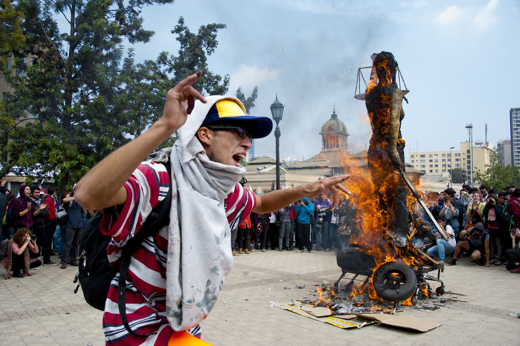 Description of . Students burn an effigy during a protest to demand Chilean President Sebastian Pinera\'s government to improve the public education quality, in Santiago, on April 11,2013. MARTIN BERNETTI/AFP/Getty Images