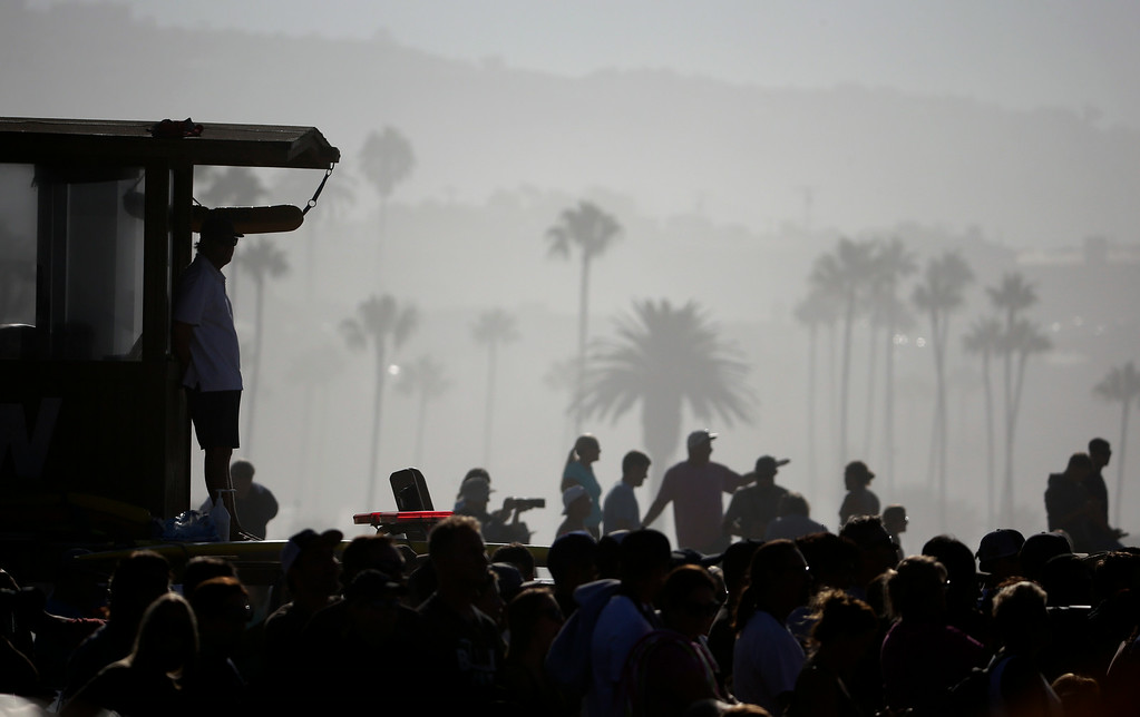 Description of . A lifeguard watches surfers ride waves at the wedge on Wednesday, Aug. 27, 2014 in Newport Beach, Calif. Beach goers experienced much higher than normal surf, brought on by Hurricane Marie spinning off the coast on Mexico. (AP Photo/Chris Carlson)