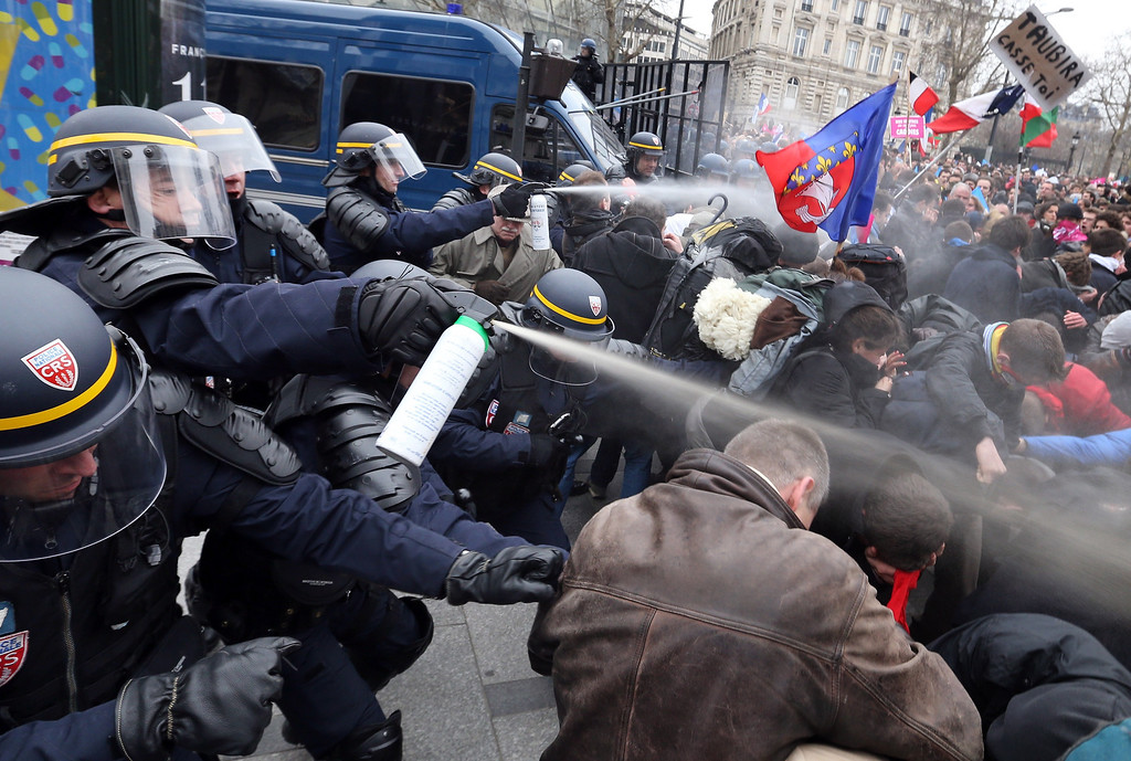 Description of . Riot police spray tear gas on demonstrators during clashes on the Champs-Elysees avenue in Paris, on March 24, 2013, as thousands of people demonstrated against France's gay marriage law in an attempt to block legislation that would allow homosexual couples to marry and adopt children.  THOMAS SAMSON/AFP/Getty Images