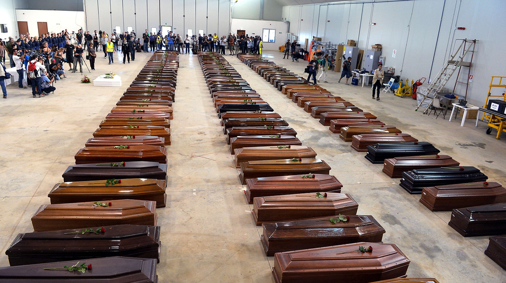 Description of . Coffin of victims are seen in an hangar of Lampedusa airport on October 5, 2013, after a boat with migrants sank, killing more than a hundred people. Italy mourned the African asylum-seekers feared dead in the worst ever Mediterranean refugee disaster, as the government appealed for Europe to stem the influx of migrants.  ALBERTO PIZZOLI/AFP/Getty Images