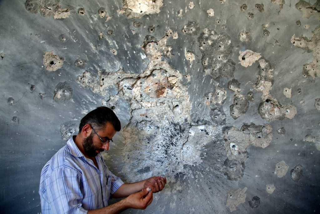 Description of . FILE - A Syrian man holds bullets he picked from the wall of a damaged house in the town of Atareb, on the outskirts of Aleppo, Syria, Sunday, Aug. 5, 2012. (AP Photo/Khalil Hamra, File)