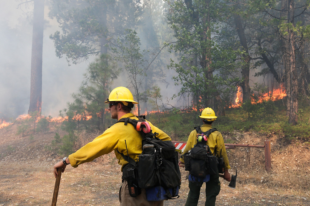 Description of . Two firefighters watch trees burn while battling the Rim Fire near Yosemite National Park, Calif., on Monday, Aug. 26, 2013. Crews working to contain one of California's largest-ever wildfires gained some ground Monday against the flames threatening San Francisco's water supply, several towns near Yosemite National Park and historic giant sequoias. (AP Photo/Jae C. Hong)