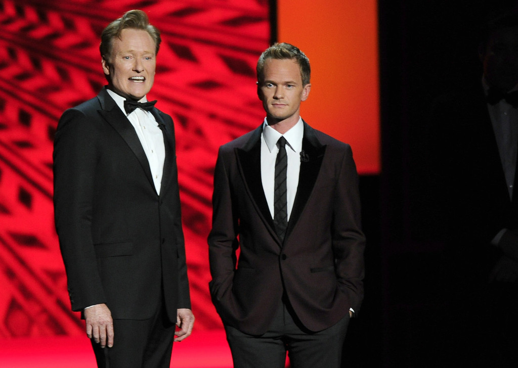 Description of . Conan O'Brien, left, and  Neil Patrick Harris appear on stage at the 65th Primetime Emmy Awards at Nokia Theatre on Sunday Sept. 22, 2013, in Los Angeles.  (Photo by Chris Pizzello/Invision/AP)