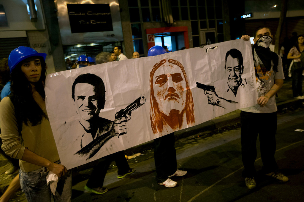 Description of . People protest holding a banner with drawings of Rio de Janeiro's Governor Sergio Cabral, right, and Mayor Eduardo Paes aiming guns to Christ the Redeemer  as Rio's main symbol,  in Rio de Janeiro, Brazil, Monday, June 17, 2013. Protests in Sao Paulo, Rio de Janeiro and other Brazilian cities, set off by a 10-cent hike in public transport fares, have clearly moved beyond that issue to tap into widespread frustration in Brazil about a heavy tax burden, politicians widely viewed as corrupt and woeful public education, health and transport systems and come as the nation hosts the Confederations Cup soccer tournament and prepares for next month's papal visit. (AP Photo/Silvia Izquierdo)