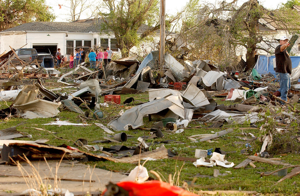 Description of . Quapaw, Okla.,  residents survey the damage in a residential neighborhood struck by a tornado on Sunday evening, April 27, 2014. A powerful storm system rumbled through the central and southern United States on Sunday, spawning a massive tornado that carved path of destruction through the northern Little Rock suburbs and another twister that killed two people in Oklahoma and injured others in Kansas. (AP Photo/Tulsa World,  Gary Crow)