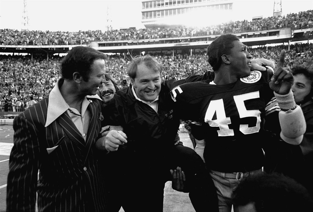 Description of . ** FILE ** In this Jan. 18, 1976, file photo, Pittsburgh Steelers coach Chuck Noll, center, leaves the field with Jim Allen (45) who holds up his finger indicating the Steelers are No. 1 after defeating the Dallas Cowboys 21-17 in Super Bowl X at the Orange Bowl in Miami. Now that Pittsburgh is headed to its seventh Super Bowl, each of the Steelers' three coaches in the last 40 years has taken them there. Noll first got there in his sixth season in 1974, Bill Cowher in his fourth. Mike Tomlin needed only two years after unexpectedly being hired for one of the best-known coaching jobs in American pro sports. (AP Photo/Phil Sandlin, File)