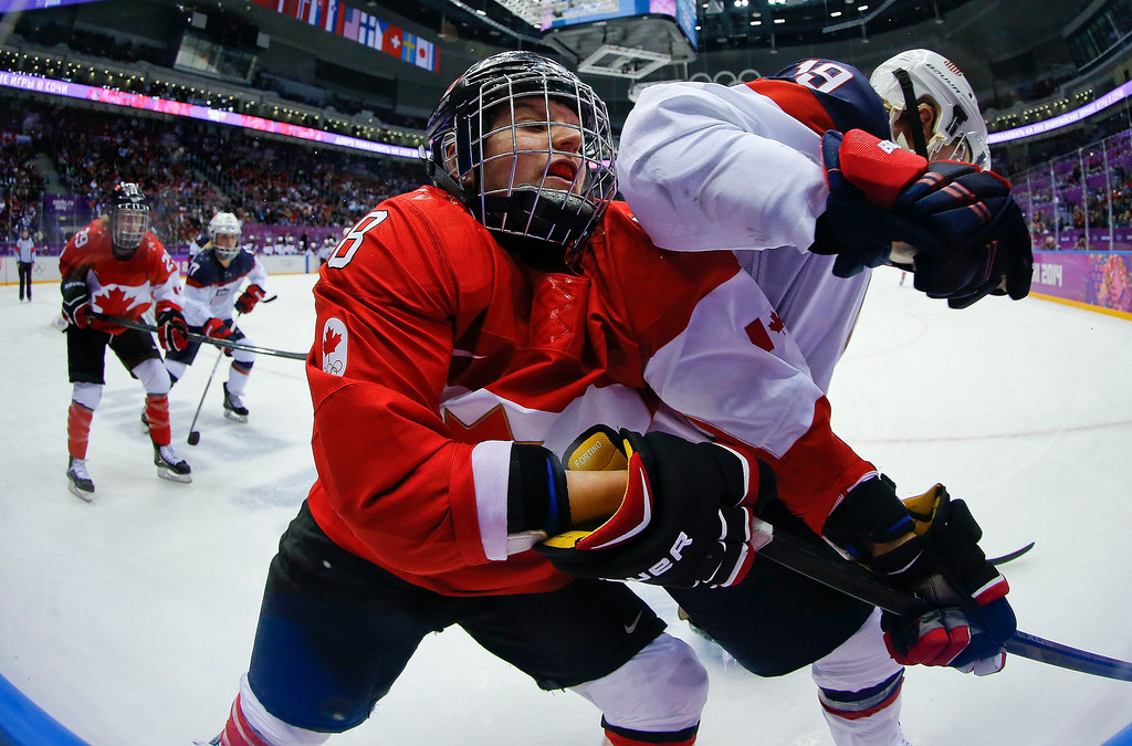 Description of . Laura Fortino of Canada (8) gets an elbow in her mask from Jocelyne Lamoureux of the United States (17) during the third period of the women's gold medal ice hockey game at the 2014 Winter Olympics, Thursday, Feb. 20, 2014, in Sochi, Russia. (AP Photo/Matt Slocum)