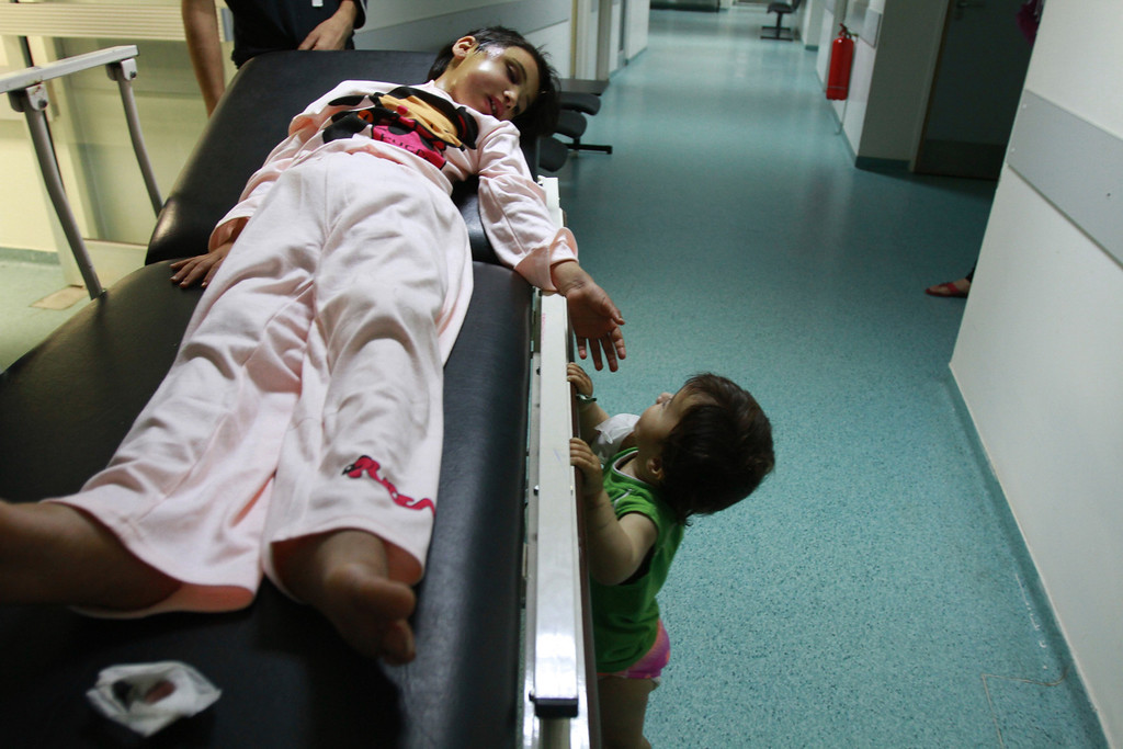 Description of . Shams al-Mohamad, a 6-year-old Syrian girl, lies on a stretcher as she looks at her sister Marwa at a hospital in Tripoli, northern Lebanon, June 14, 2012. According to their mother, Shams and Marwa were wounded when a shell hit their house during fighting between Syrian troops and anti-government forces in the Syrian town of Qusair. REUTERS/Omar Ibrahim