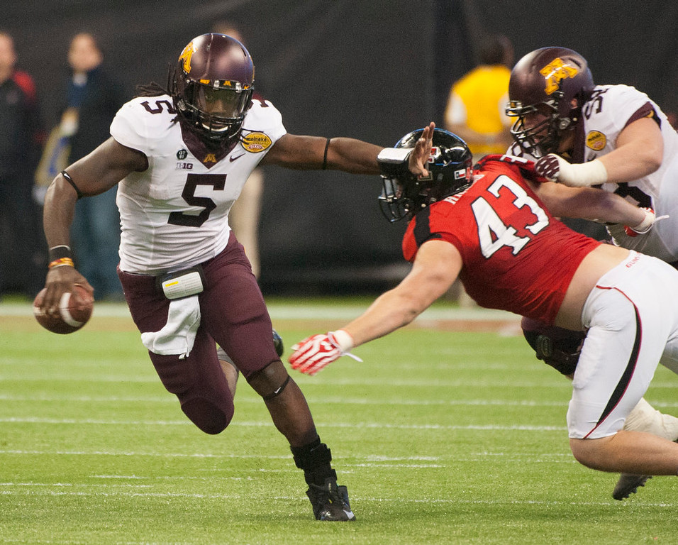 Description of . Minnesota's MarQueis Gray (5) runs by Texas Tech's Jackson Richards (43) during the second quarter of the Meineke Car Care Bowl NCAA college football game, Friday, Dec. 28, 2012, in Houston. (AP Photo/Dave Einsel)