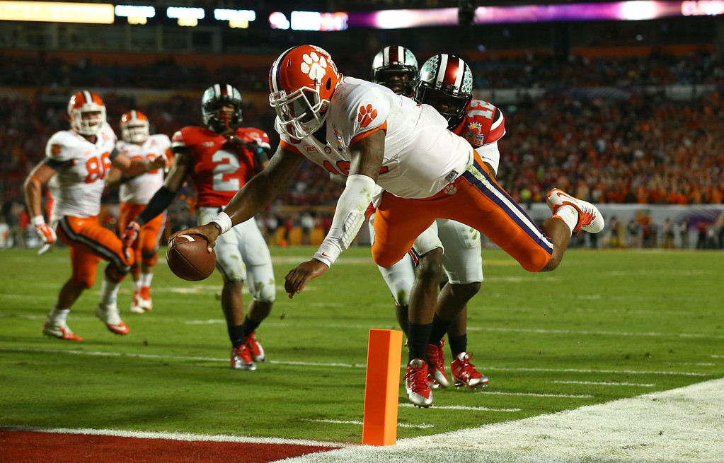 Description of . MIAMI GARDENS, FL - JANUARY 03: Tajh Boyd #10 of the Clemson Tigers dives for the endzone attempting to score a touchdown in the fourth quarter against the Ohio State Buckeyes during the Discover Orange Bowl at Sun Life Stadium on January 3, 2014 in Miami Gardens, Florida. Boyd stepped out of bounds on the play and was ruled down. (Photo by Streeter Lecka/Getty Images)