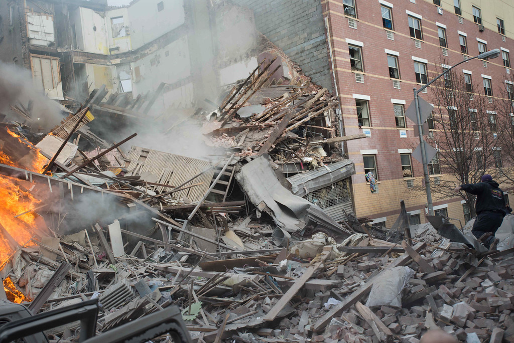 Description of . Emergency workers respond to the scene of an explosion and building collapse in the East Harlem neighborhood of New York, Wednesday, March 12, 2014.  (AP Photo/Jeremy Sailing)