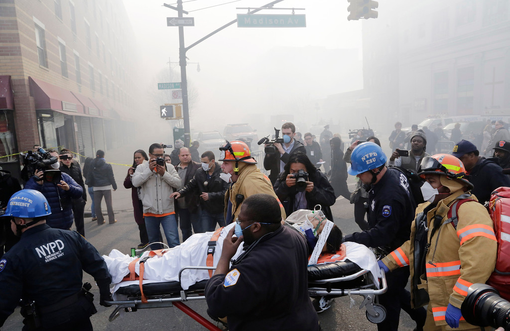 Description of . Rescue workers remove an injured person on a stretcher after a possible explosion and building collapse in the East Harlem neighborhood of New York, Wednesday, March 12, 2014 (AP Photo/Mark Lennihan)