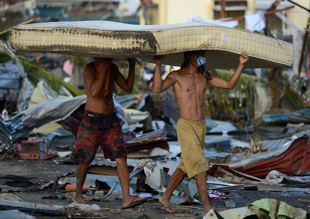 Description of . Residents carry a mattress taken from a hotel in Palo, eastern island of Leyte on November 10, 2013, three days after devastating Super Typhoon Haiyan hit the area on November 8. The death toll from a super typhoon that decimated entire towns in the Philippines could soar well over 10,000, authorities warned on November 10, making it the country's worst recorded natural disaster. NOEL CELIS/AFP/Getty Images