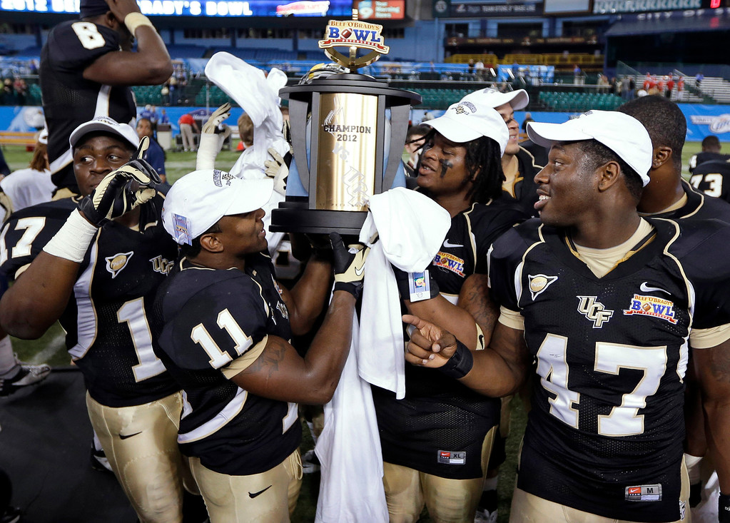 Description of . Central Florida players, from left, Cedric Thompson, Jonathan Davis, E.J. Dunston, and Deion Green celebrate with the trophy after Central Florida defeated Ball State 38-17 during the Beef 'O' Brady's Bowl NCAA college football game Friday, Dec. 21, 2012, in St Petersburg, Fla. (AP Photo/Chris O'Meara)