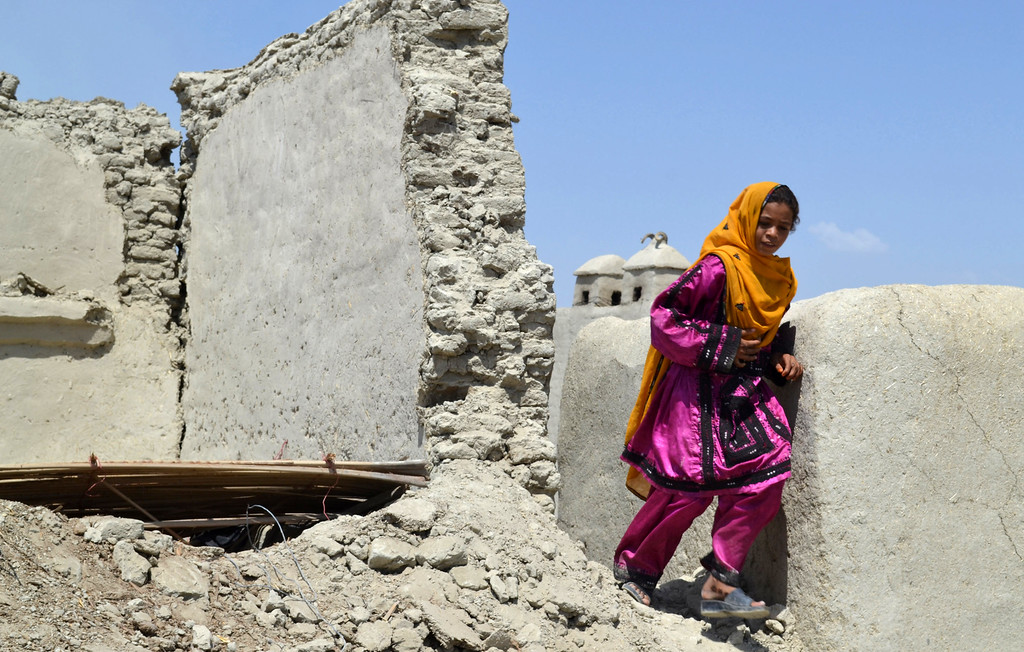 Description of . A Pakistani girl walks past a collapsed house following an earthquake in Labach, the remote district of Awaran in Baluchistan province, Pakistan, Thursday, Sept. 26, 2013.  (AP Photo/Arshad Butt)