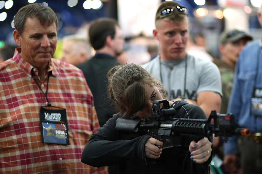 Description of . HOUSTON, TX - MAY 03:  An attendee uses a gun to play a shooting game during the 2013 NRA Annual Meeting and Exhibits at the George R. Brown Convention Center on May 3, 2013 in Houston, Texas.  More than 70,000 peope are expected to attend the NRA's 3-day annual meeting that features nearly 550 exhibitors, gun trade show and a political rally. The Show runs from May 3-5.  (Photo by Justin Sullivan/Getty Images)