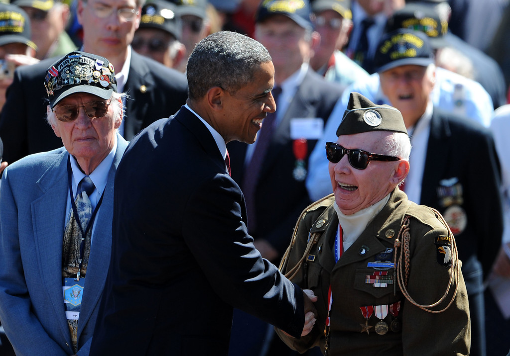 Description of . U.S. President Barack Obama joins WWII Veterans during a ceremony at the Normandy American Cemetery on the 70th anniversary of D-Day June 6, 2014 in Colleville-sur-Mer, France. (Photo by Antoine Antoniol/Getty Images)