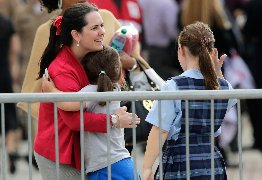 Description of . A woman hugs her child while reuniting at a gathering point for family members of Navy Yard employees that was set up inside Nationals Park in the wake of the shooting September 16, 2013 in Washington, DC. Police believe at least one gunman shot and killed at least 12 people and wounded others in an incident that put parts of the city on lockdown. (Photo by Win McNamee/Getty Images)