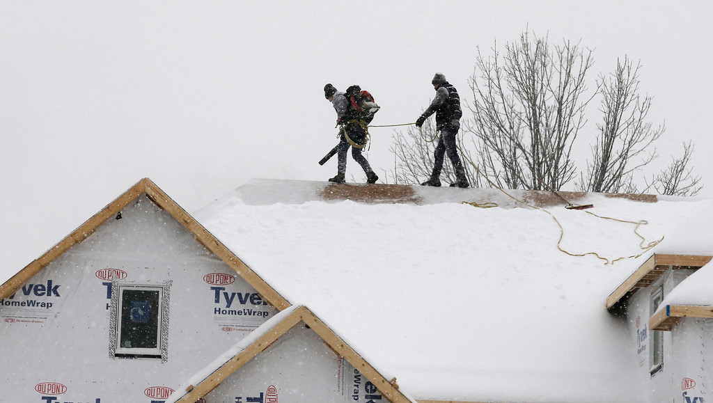 Description of . Two men clear snow from a roof of a new home with a leaf blower, Wednesday, Feb. 5, 2014, in Pepper Pike, Ohio. Most of Ohio was hit with another bout of heavy snow and freezing rain, closing hundreds of schools and creating extremely hazardous driving conditions. Much of the state was slammed with 4 to 8 inches of snow overnight.  (AP Photo/Tony Dejak)