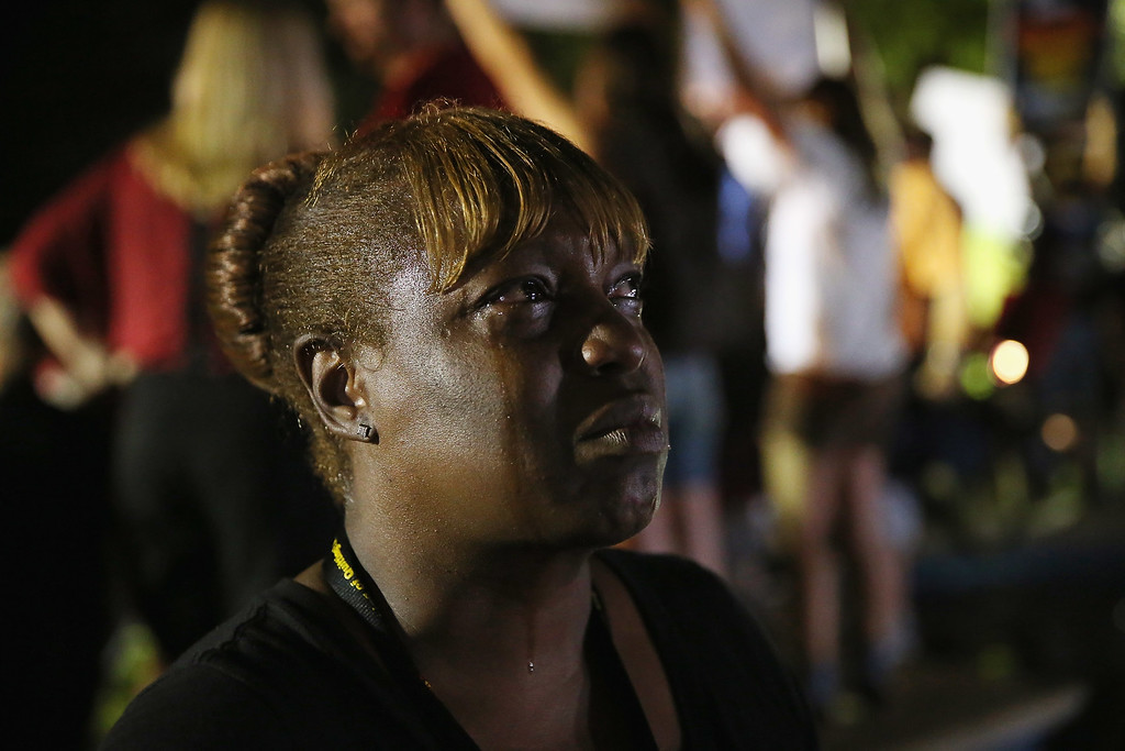 Description of . SANFORD, FL - JULY 13: Tanetta Foster breaks into tears in front of the Seminole County Criminal Justice Center after learning George Zimmerman had been found not guilty in the Murder of Trayvon Martin on July 13, 2013 in Sanford, Florida. Zimmerman, a neighborhood watch volunteer shot and killed 17-year-old Martin after an altercation in February 2012.  (Photo by Scott Olson/Getty Images)