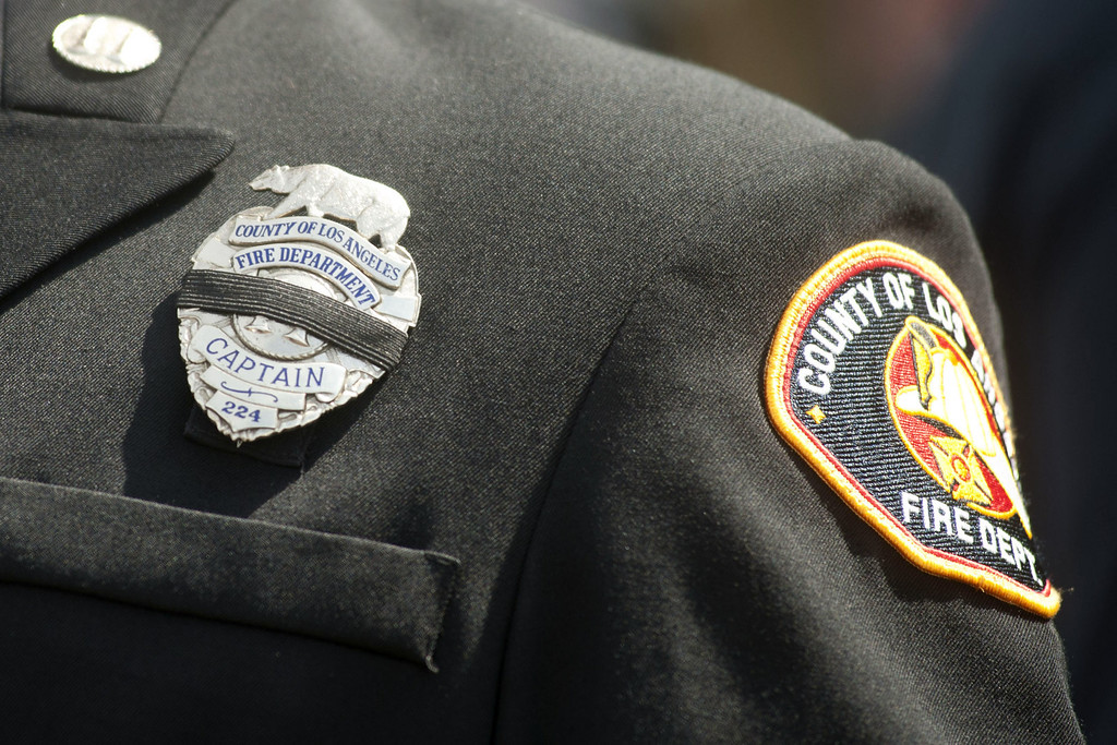 Description of . Members of fire departments from around the country attend a memorial in honor of the 19 firefighters killed in a wildfire, at Tim's Toyota Center July 9, 2013 in Prescott Valley, Arizona. (Photo by Laura Segall/Getty Images)
