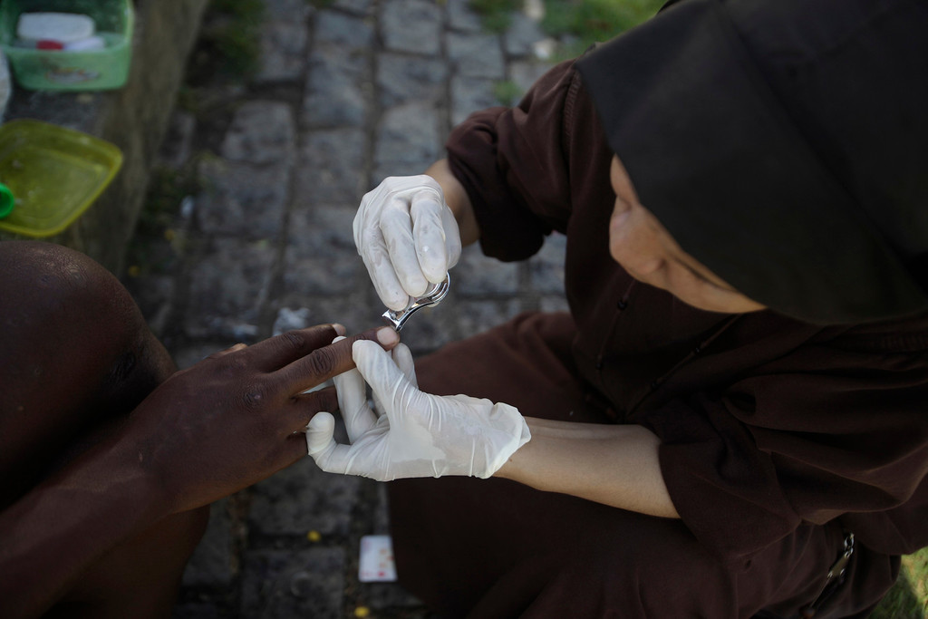 Description of . Sister Filoteia, a member of the Franciscan fraternity O Caminho, cuts a homeless person's nails in the Campo Grande neighbourhood of Rio de Janeiro, April 16, 2013. O Caminho (The Way) are a group of Franciscan monks and nuns who help the homeless on the streets of Rio de Janeiro. They consider the election of Pope Francis, the first pontiff to take the name of St Francis of Assisi, to be a confirmation of their beliefs in poverty and simplicity. In July, Pope Francis will visit Rio de Janeiro in his first international trip since assuming the papacy. Picture taken April 16, 2013. REUTERS/Ricardo Moraes