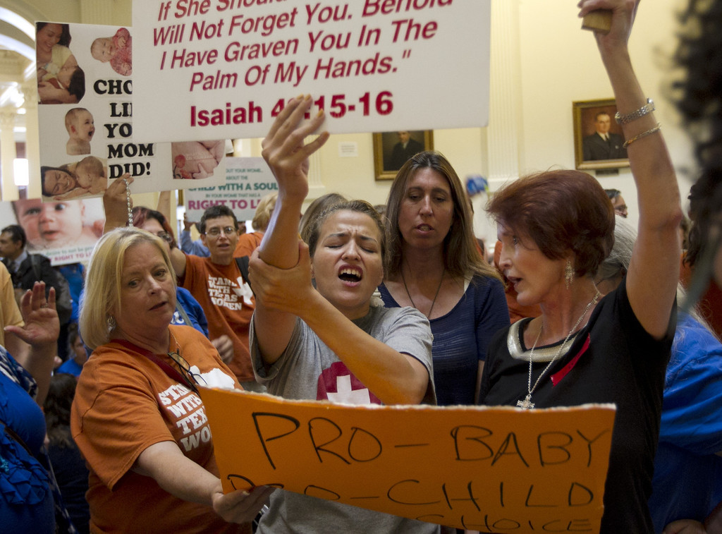 Description of . Abortion opponent Katherine Aguillar, middle, struggles to keep her sign raised during the debate of the abortion restriction bill,  Friday July 12, 2013  at the Capitol in Austin, Texas  (AP Photo/Austin American-Statesman, Jay Janner)