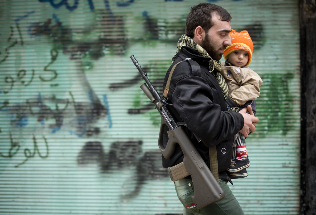 Description of . A rebel fighter carries his son after the Friday prayer in the al-Fardos neighbourhood of Aleppo on December 7, 2012. Syrian opposition groups had agreed in Doha last month to sink their differences and form a single body in the hope of getting direct aid, including crucial anti-aircraft weapons, to combat President Assad. ODD ANDERSEN/AFP/Getty Images