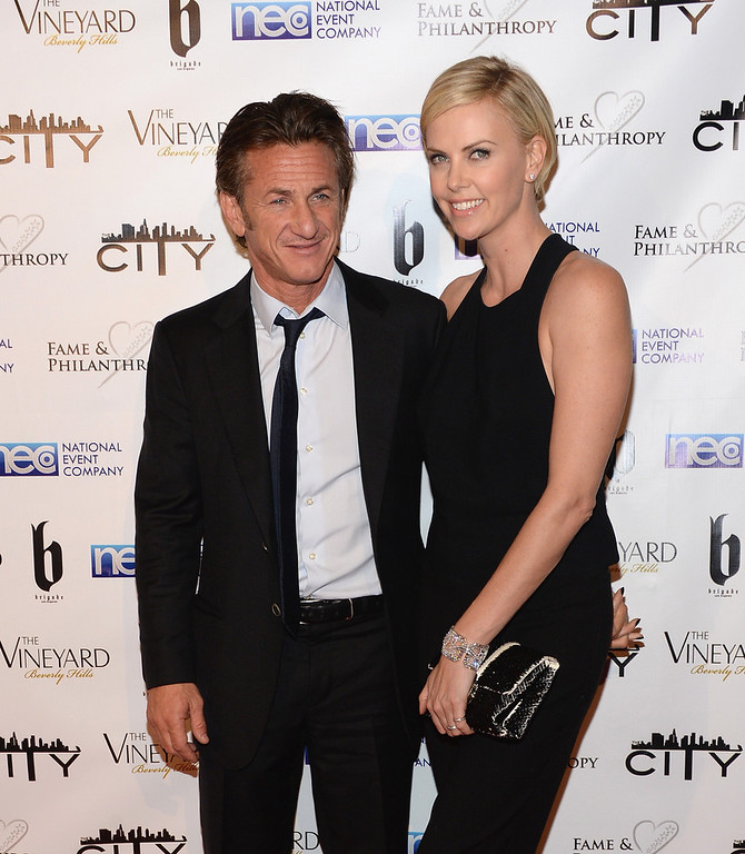 Description of . Sean Penn and Charlize Theron attend the Fame and Philanthropy Post-Oscar Party at The Vineyard on March 2, 2014 in Beverly Hills, California.  (Photo by Jason Kempin/Getty Images)