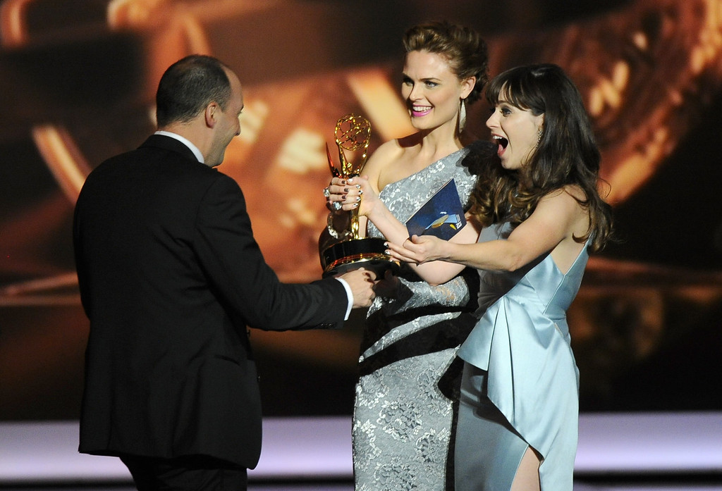 Description of . Zooey Deschanel, right, and Emily Deschanel present the award for outstanding supporting actor in a comedy series to Tony Hale, left, on stage at the 65th Primetime Emmy Awards at Nokia Theatre on Sunday Sept. 22, 2013, in Los Angeles.  (Photo by Chris Pizzello/Invision/AP)