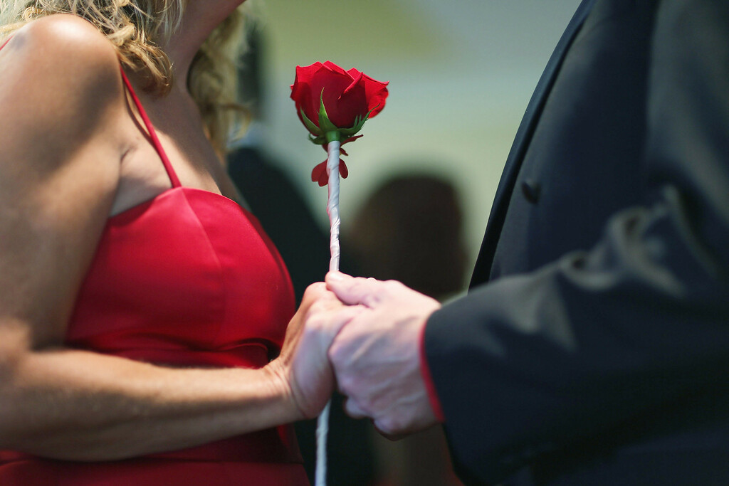 . Karen Brown (L) and Douglas Brown hold hands as they are wed during a group Valentine\'s day wedding at the National Croquet Center on February 14, 2013 in West Palm Beach, Florida. The group wedding ceremony is put on by the Palm Beach Country Clerk & Comptroller\'s office and approximately 40 couples tied the knot.  (Photo by Joe Raedle/Getty Images)