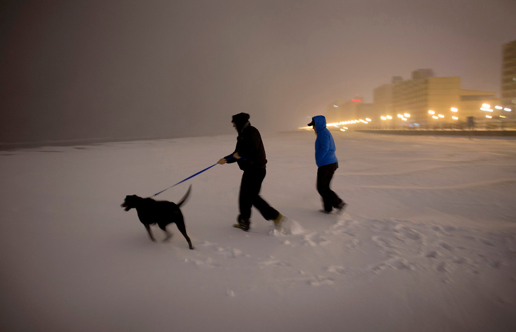 Description of . With a winter storm making its way over southeast Virginia late Jan. 28, 2014, Sean Cantrell, center, and his wife Megan Cantrell venture out onto the snowy Virginia Beach oceanfront for a look with there dog Griffin. (AP Photo/The Virginian-Pilot, L. Todd Spencer)