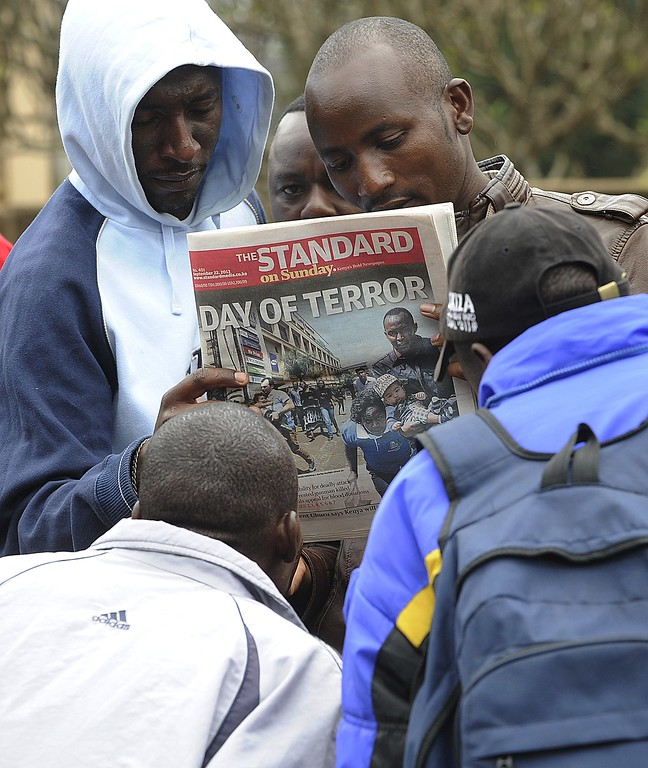 Description of . Kenyans look on September 22, 2013 at a local daily newspaper with the front page featuring the bloodbath at the Westgate mall in Nairobi.  AFP PHOTO / SIMON  MAINA/AFP/Getty Images