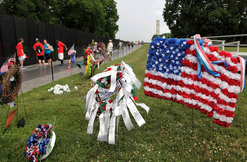 Description of . The U.S. national flag composed of flowers is placed near the Vietnam Veterans Memorial wall etched with names of more than 58,000 U.S. servicemen and women who died in the war, in Washington May 23, 2013. Memorial Day will fall on May 27 this year.    REUTERS/Yuri Gripas