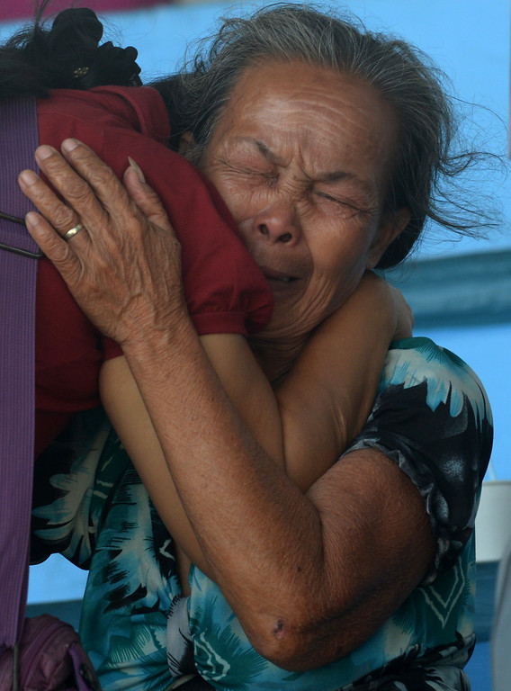 Description of . Sherlete Go (top) hugs her mother Rosing Pindos who survived Super Typhoon Haiyan in the central coastal city of Tacloban, after arriving on a US KC-130 military cargo plane that flew them out of the city to Manila on November 16, 2013.  AFP PHOTO / Jay  DIRECTO/AFP/Getty Images