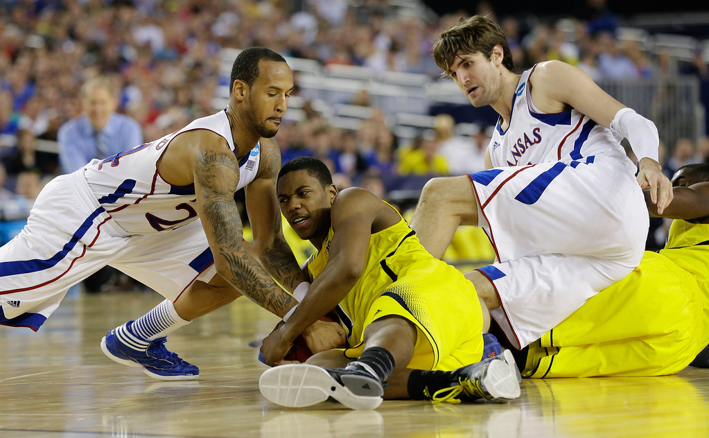 Description of . Michigan\'s Glenn Robinson III ,battles for a loose ball with Kansas\' Travis Releford, and Jeff Withey, right, during the second half of a regional semifinal game in the NCAA college basketball tournament, Friday, March 29, 2013, in Arlington, Texas. (AP Photo/Tony Gutierrez)