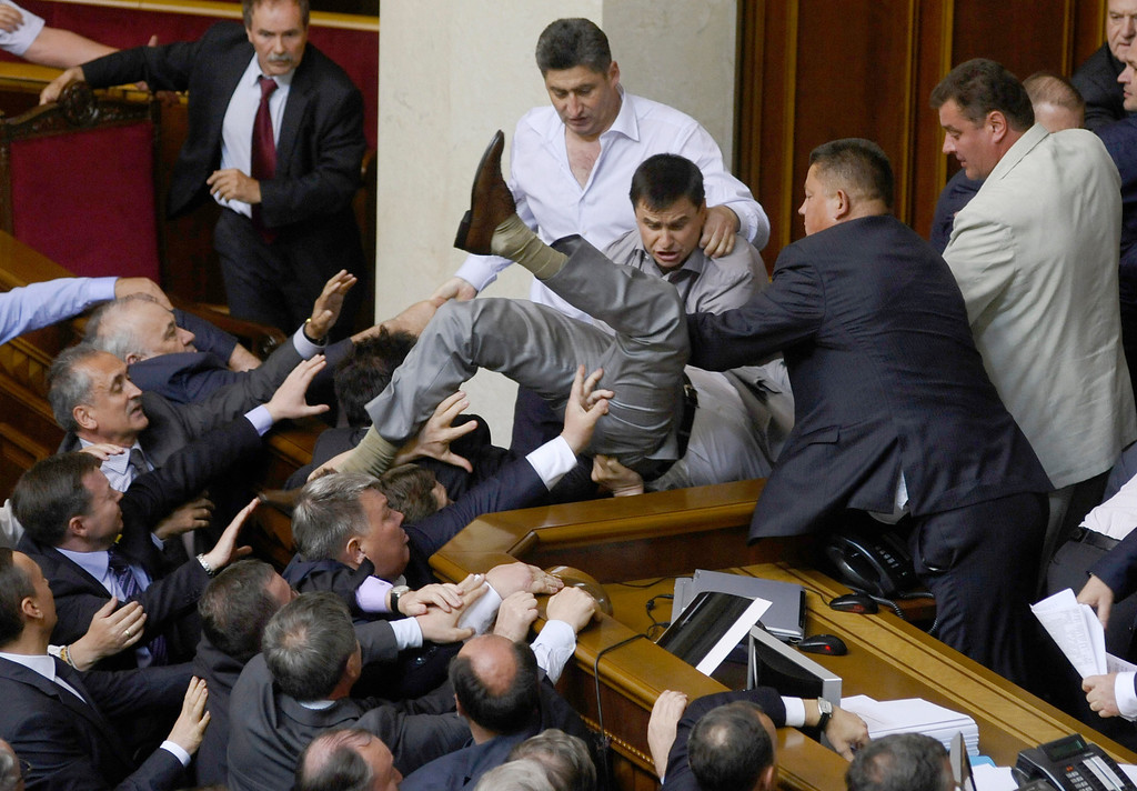 Description of . In this may 24, 2012 file photo, lawmakers scuffle from pro-presidential and oppositional factions in the parliament session hall in Kiev, Ukraine. The hall erupted over a bill that would allow the use of the Russian language in courts, hospitals and other institutions in the Russian-speaking regions of the country. (AP Photo/Maks Levin, File)