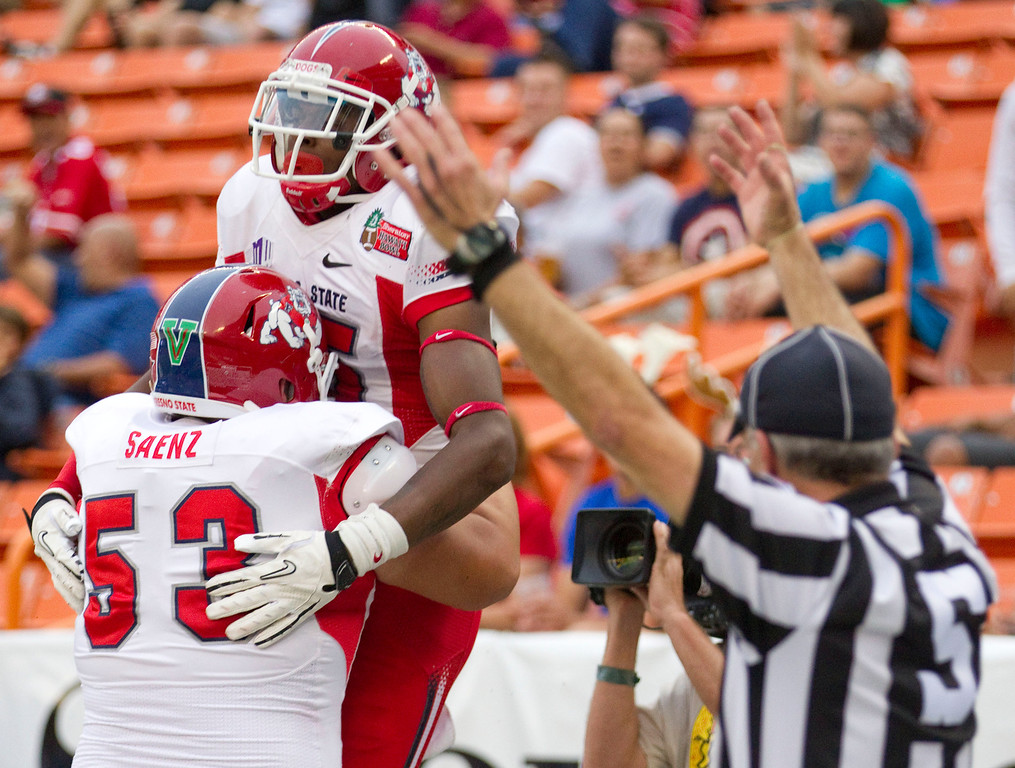 Description of . Fresno State offensive linesman Mike Saenz (53) picks up wide receiver Davante Adams (15) after Adams' touchdown reception in the third quarter against SMU in the Hawaii Bowl, an NCAA college football game Monday, Dec. 24, 2012, in Honolulu. (AP Photo/Eugene Tanner)