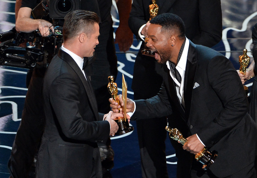 Description of . Actor/producer Brad Pitt (L) accepts the Best Picture award for '12 Years a Slave' from actor Will Smith onstage during the Oscars at the Dolby Theatre on March 2, 2014 in Hollywood, California.  (Photo by Kevin Winter/Getty Images)