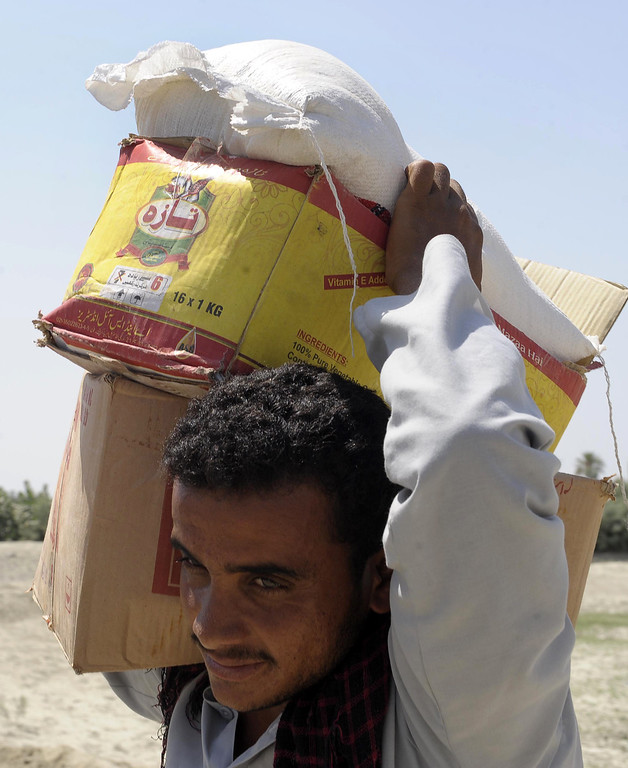 Description of . A Pakistani earthquake survivor carries relief food supplies at Labach area, in the earthquake-devastated district of Awaran on September 26, 2013.  AFP PHOTO / Banaras KHAN/AFP/Getty Images