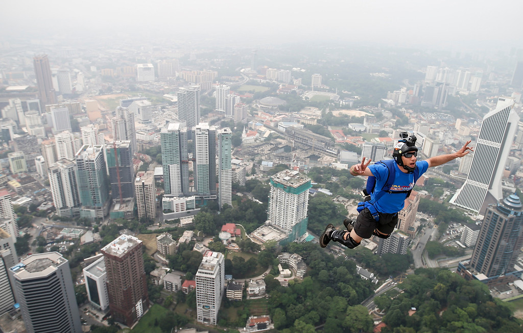 Description of . Base jumper Kieran Francis Tomlinson of Australia's leaps from the 300-meter Open Deck of the Malaysia's landmark Kuala Lumpur Tower during the International Tower Jump in Kuala Lumpur, Friday, Sept. 27, 2013.  (AP Photo/Vincent Thian)