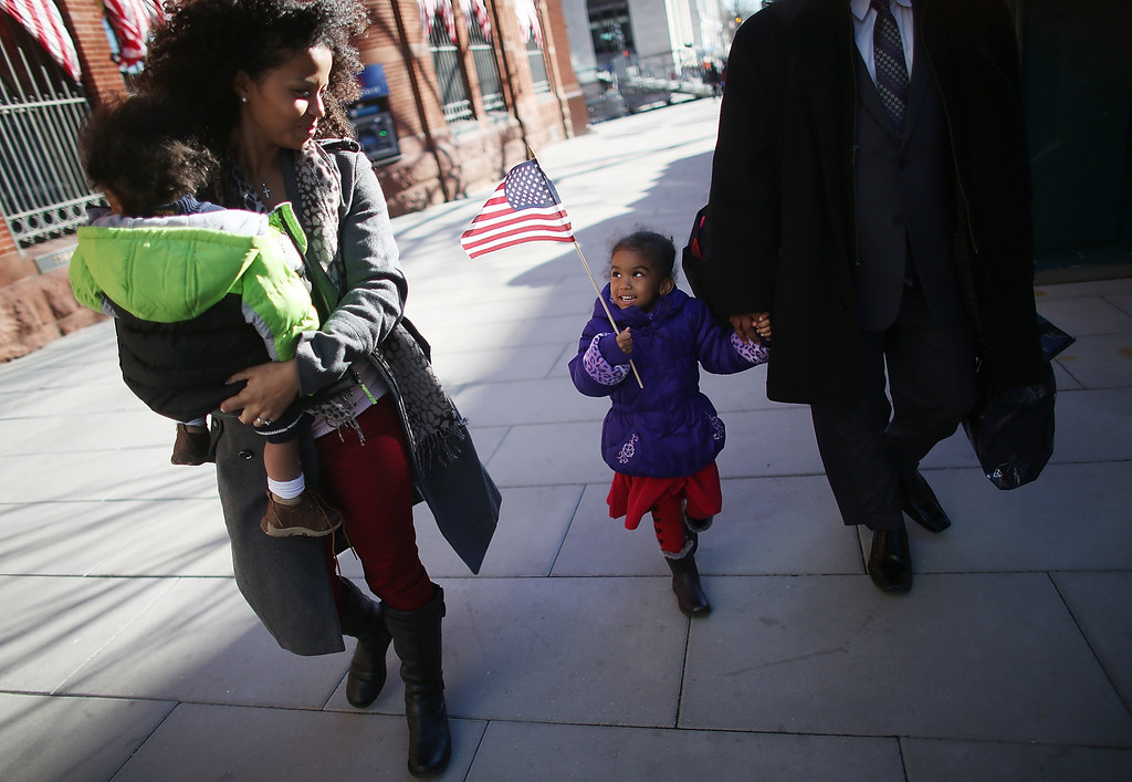 . Ariana Smith carries an American flag as mother Ana Blanco-Smith carries Christian Smith as Washington prepares for President Barack Obama\'s second inauguration on January 20, 2013 in Washington, DC. The family travelled from Florida to attend the inauguration. One day before the public inaugural ceremony at the U.S. Captiol on January 21, Obama was officially sworn in for his second term during a private ceremony surrounded by friends and family in the Blue Room of the White House.  (Photo by Mario Tama/Getty Images)