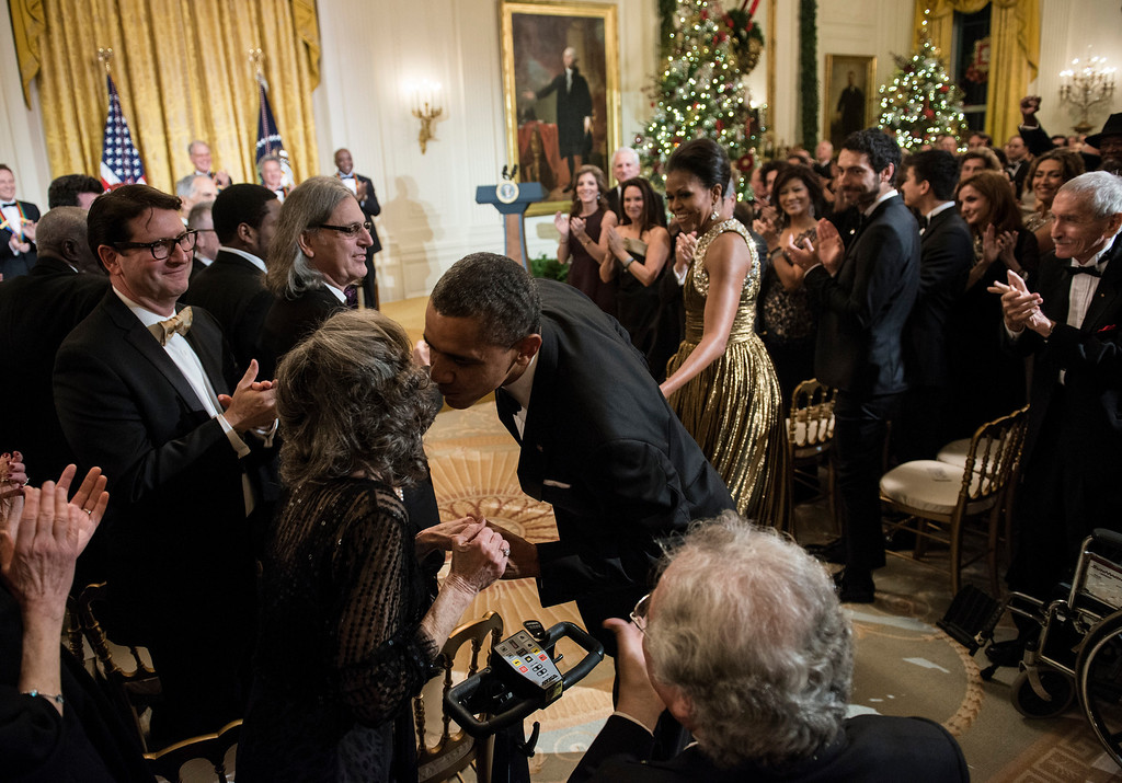 Description of . US President Barack Obama kisses Toby Perlman while arriving with US First Lady Michelle Obama during an event in the East Room of the White House December 2, 2012 in Washington, DC. Obama and US first lady Michelle Obama attended the event at the White House with the 2012 Kennedy Center Honorees before to celebrate their contribution to the arts before heading to the Kennedy Center for the honors program.  BRENDAN SMIALOWSKI/AFP/Getty Images