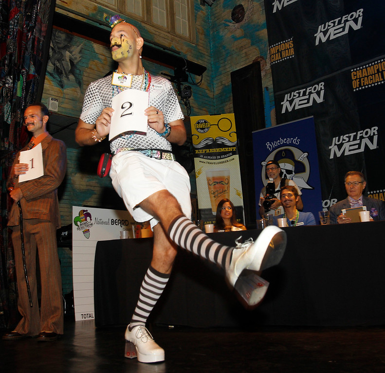 Description of . As contestant number one Ian Stetler, far left, waits his turn, Keith Haubrich of Seattle, Wash., struts his stuff in the Dali Moustache division during the fourth annual Just For Men National Beard and Moustache Championships Saturday, Sept. 7, 2013 in New Orleans. Haubrich went on to win the gold medal for the Dali division. Contestants competed in 18 different categories including Dali, full beard natural and sideburns. (AP Photo/Susan Poag)