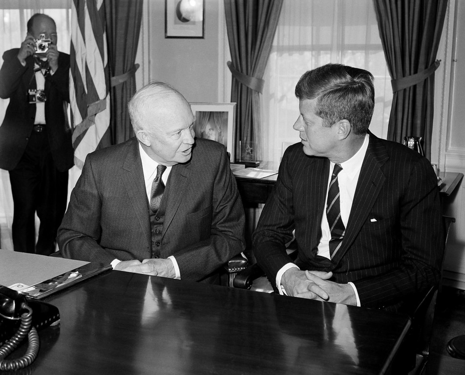Description of . President-elect Kennedy listens as President Dwight Eisenhower comments at the White House on Dec. 6, 1960. Eisenhower later took Kennedy  on a tour of the Executive Mansion. Associated Press file
