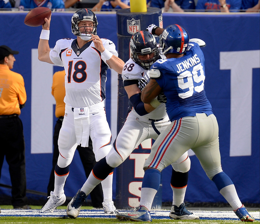 Description of . Quarterback Peyton Manning (18) of the Denver Broncos looks to throw downfield against the New York Giants September 15, 2013 MetLIFE Stadium. (Photo by John Leyba/The Denver Post)