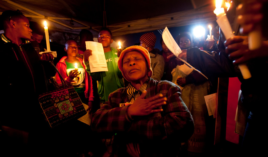 Description of . A group of wellwishers sing and pray for the health of Nelson Mandela at night outside the Mediclinic Heart Hospital where former South African President Nelson Mandela is being treated in Pretoria, South Africa Friday, June 28, 2013. As Nelson Mandela remained in critical condition in hospital Friday, a family feud over where the 94-year-old former president should be buried went to the courts, according to South Africa's national broadcaster. (AP Photo/Ben Curtis)