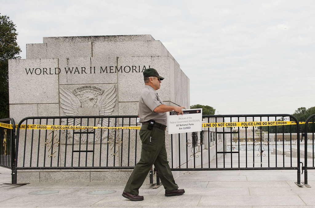 Description of . US Park Ranger Richard Trott places a closed sign on a barricade in front of the World War II Memorial monument in Washington, DC, October 1, 2013.        AFP PHOTO/Jim  WATSON/AFP/Getty Images